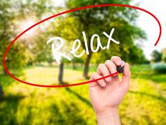 Man Hand writing Relax with black marker on visual screen. - stock photo