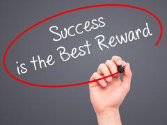 Man Hand writing Success is the Best Reward with black marker - stock photo