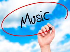 Man Hand writing Music with black marker on visual screen. Stock Photos