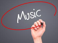 Man Hand writing Music with black marker on visual screen. - stock photo