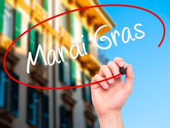 Stock Photo of Man Hand writing Mardi Gras with black marker on visual screen.