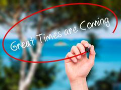 Man Hand writing Great Times are Coming with black marker on visual screen - stock photo