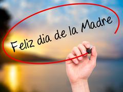 Hand writing Feliz dia de la Madre (Happy Mothers Day in Spanish) with marker - stock photo