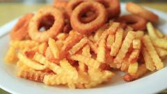 Fried potatoes and onion rings Stock Footage