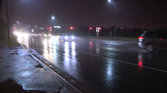 Cars driving at night on wet city streets with poor visibility in the dark Stock Footage