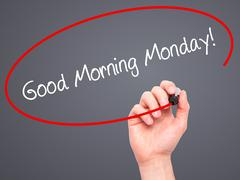 Man Hand writing Good Morning Monday! with black marker on visual screen. Stock Photos
