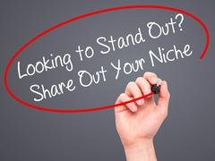 Man Hand writing Looking to Stand Out? Share Out Your Niche with black marker - stock photo