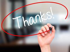 Man Hand writing Thanks! with black marker on visual screen. Stock Photos
