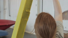 Woman painting metal frame yellow in industrial warehouse Stock Footage