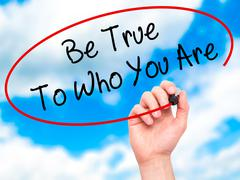 Man Hand writing Be True To Who You Are with black marker on visual screen. - stock photo