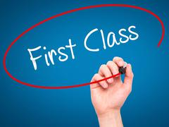 Stock Photo of Man Hand writing First Class with black marker on visual screen