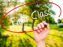 Man Hand writing First Class with black marker on visual screen Stock Photos