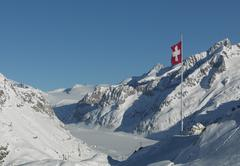 Flag over snowy slopes in remote mountains Stock Photos