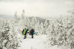 Caucasian hikers walking in snowy forest - stock photo