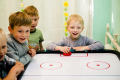 Caucasian boys playing air hockey Stock Photos