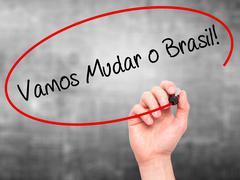 Man Hand writing Vamos Mudar o Brasil! (Let's Change Brazil in Portuguese) - stock photo