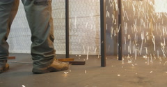 Sparks from metal grinder fall at workman's boots Stock Footage