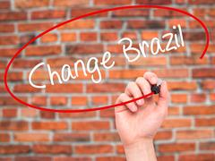 Stock Photo of Man Hand writing Change Brazil with black marker on visual screen.