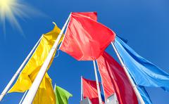 Colorful flags fluttering on the blue sky background Stock Photos