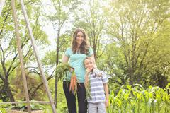 Caucasian mother and son holding carrots in garden Stock Photos