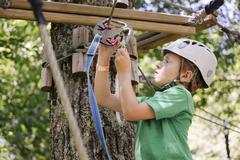 Caucasian boy hooking harness to zip Stock Photos