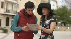 Young man helping pretty woman to find way to hotel, showing direction on map Stock Footage