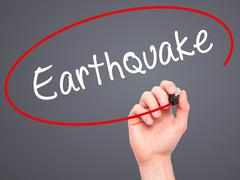 Man Hand writing Earthquake with black marker on visual screen - stock photo