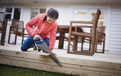 Mixed race girl sawing wood in backyard Stock Photos