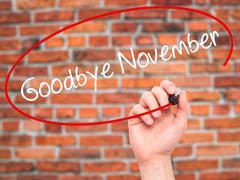 Man Hand writing Goodbye November with black marker on visual screen. Stock Photos