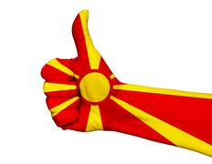 Hand with thumb up painted in colors of Macedonia flag isolated Stock Photos