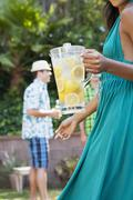 Woman holding pitcher of lemonade at backyard barbecue Stock Photos