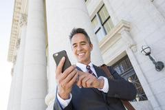Mixed race businessman using cell phone outside courthouse - stock photo