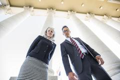 Low angle view of business people under columns Stock Photos