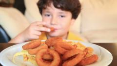 Child eating fried potatoes and crispy onion rings 2 - stock footage
