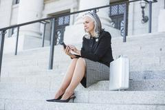 Stock Photo of Caucasian businesswoman using cell phone on courthouse steps