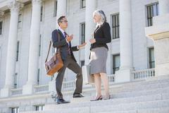 Business people talking on courthouse steps - stock photo
