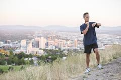 Mixed race man checking pulse on hilltop over Salt Lake City, Utah, United Stock Photos