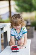 Caucasian boy playing with toy car Kuvituskuvat