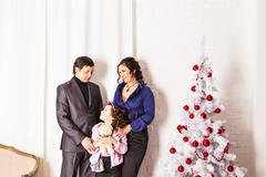 Family with gifts near Christmas tree - stock photo