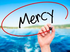 Man Hand writing Mercy with black marker on visual screen - stock photo