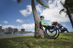 Disabled man playing in wheelchair on beach Stock Photos