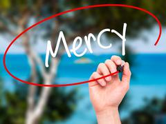 Man Hand writing Mercy with black marker on visual screen Stock Photos