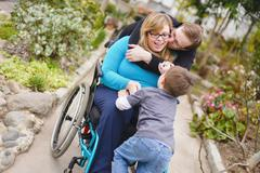Paraplegic woman and family hugging in garden Stock Photos