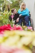 Man and paraplegic girlfriend exploring garden Stock Photos