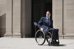Paraplegic businessman sitting in wheelchair Stock Photos