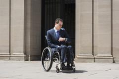 Paraplegic businessman in wheelchair checking watch Stock Photos