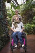 Mother pushing paraplegic daughter in wheelchair - stock photo