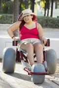 Paraplegic woman in wheelchair on walkway - stock photo