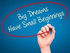 Man Hand writing Big Dreams Have Small Beginnings with marker on visual screen - stock photo