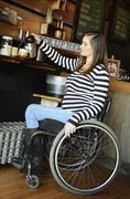 Paraplegic woman in wheelchair pouring coffee in cafe Stock Photos
